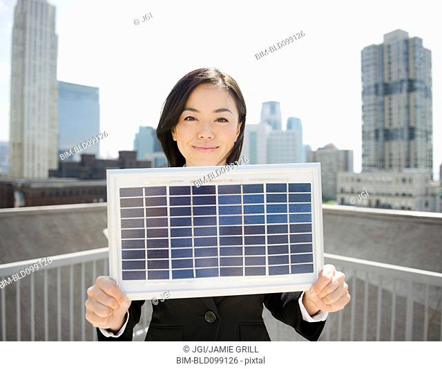 Japanese businesswoman holding solar panel outdoors