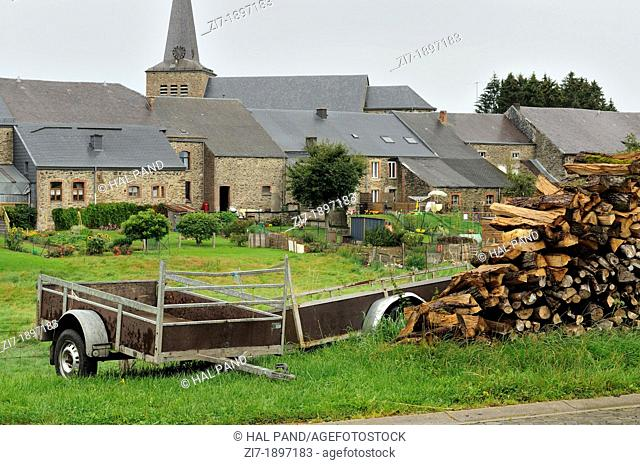 foreshortening of stack of wood and old carts in agricultural village, shot in typical cloudy light
