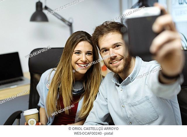 Two smiling casual coworkers in the office taking a selfie