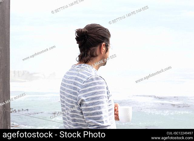 Rear view of a man holding a mug and looking out to sea