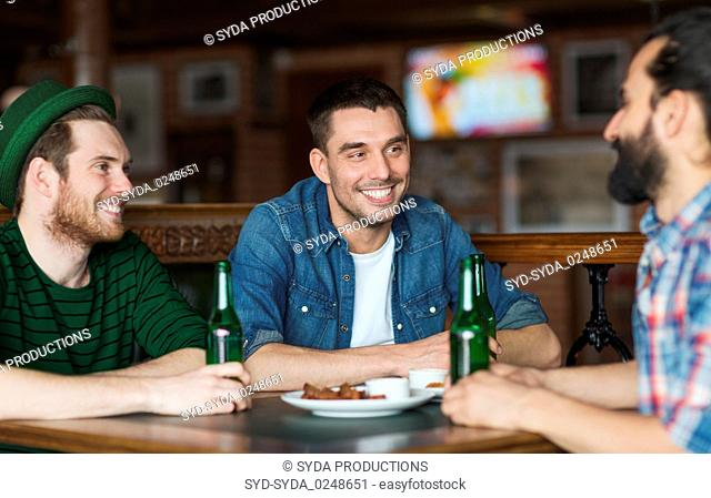 happy male friends drinking beer at bar or pub