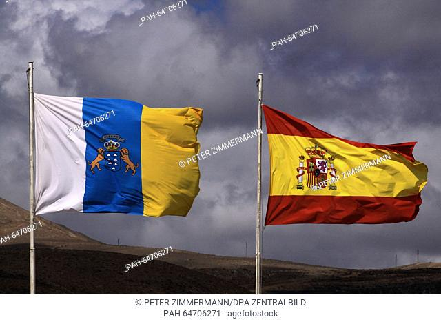 Spains national flag (R) on the Arrecife Airport on the Canary Island Lanzarote, Spain, 10 October 2015. Next to it is the flag of the Canary Islands