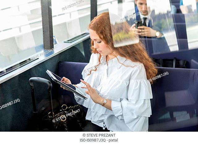 Young businesswoman using digital tablet touchscreen on passenger ferry