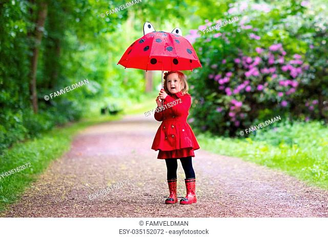 Little girl playing in rainy summer park. Child with red ladybug umbrella, waterproof coat and boots jumping in puddle and mud in the rain