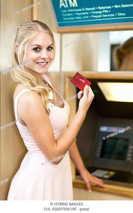 Smiling woman using ATM
