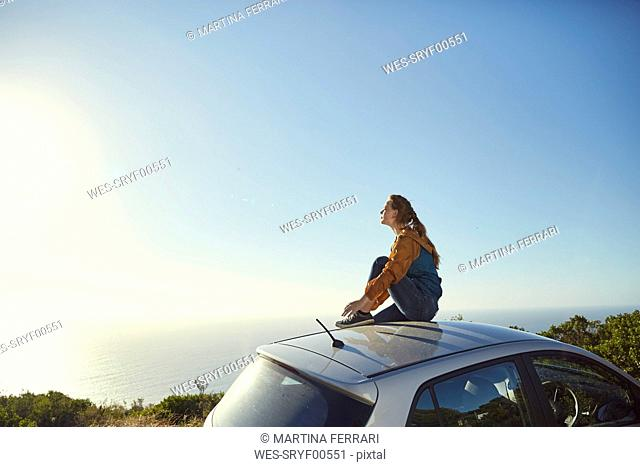 South Africa, Cape Town, Signal Hill, young woman sitting on top of car enjoying the view to the sea