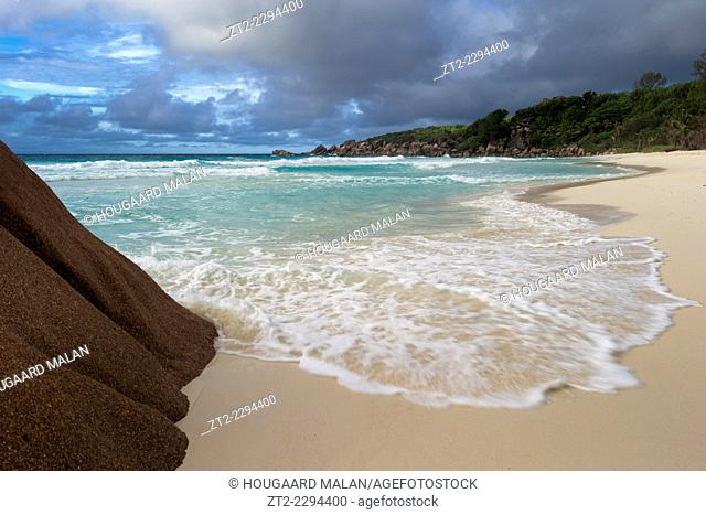 Landscape photo of a wave washing across a beach on a cloudy day. La Digue island, Seychelles