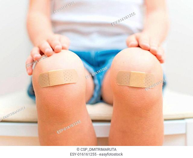 Child knee with an adhesive bandage
