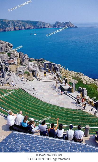 Coast. Minack Theatre site carved into cliff. Stage. Seating. People and actors. Play
