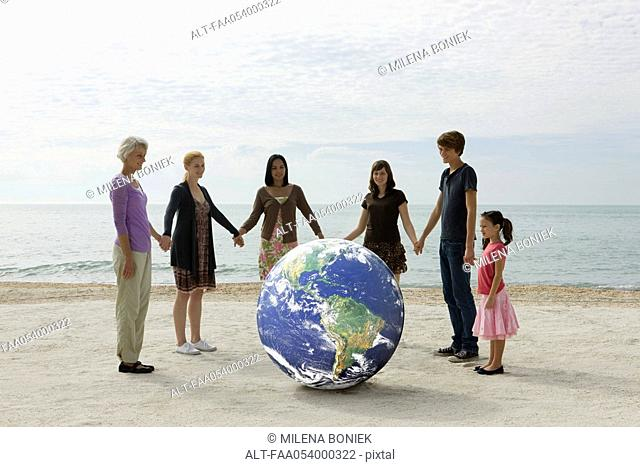Ecology concept, group of people holding hands, standing around the planet earth