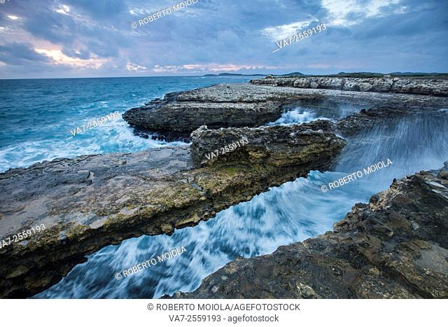 Waves crashing on Devil's Bridge. A natural arch carved by the sea from soft and hard limestone ledges of the Antigua formation