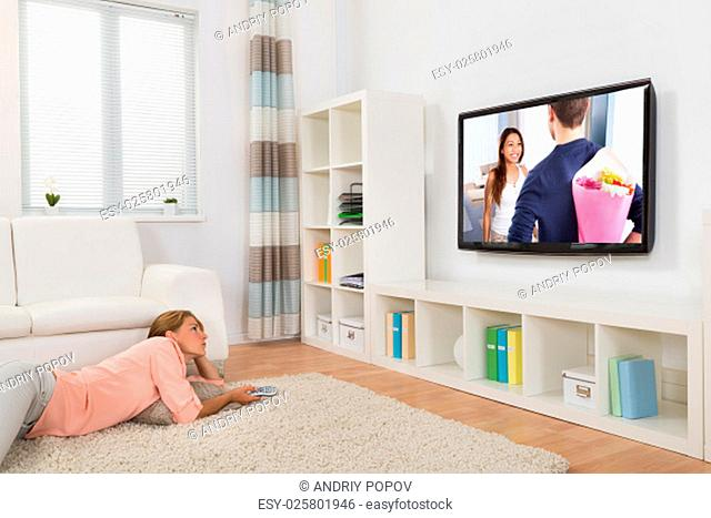 Young Woman Watching Movie While Lying On Carpet In Living Room