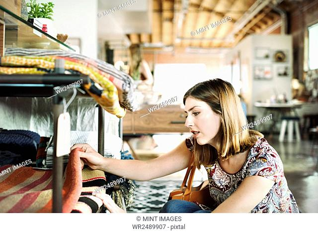 Young woman in a shop, looking at rugs on a shelf