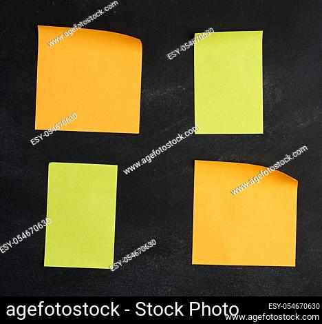 blank paper multi-colored square stickers are stuck on a black chalk board, close up