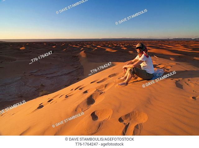 atop a sand dune in the Sahara Desert at Erg Chigaga, Morocco