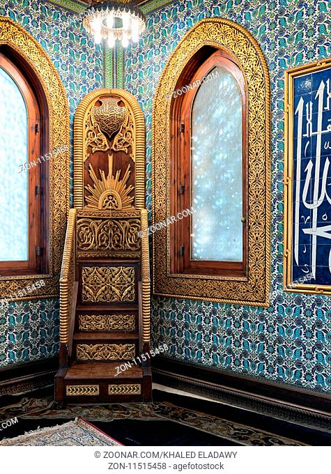 Golden ornate minbar, wooden arched window framed by golden ornate floral pattern, and floral blue pattern ceramic tiles wall at the public mosque of Manial...