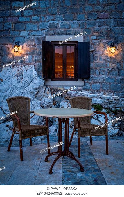 Empty table and wicker chairs outside a local cafe in Petrovac in the evening, Montenegro
