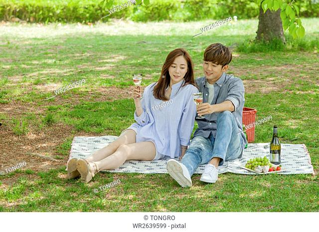 Young romantic couple having picnic at park in spring