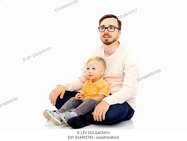family, childhood, fatherhood, leisure and people concept - happy father and and little son sitting together