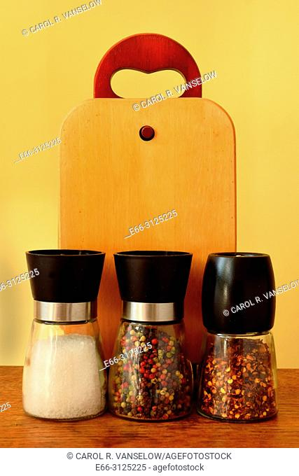 Shakers of sea salt, pepper and red peppers sitting on table