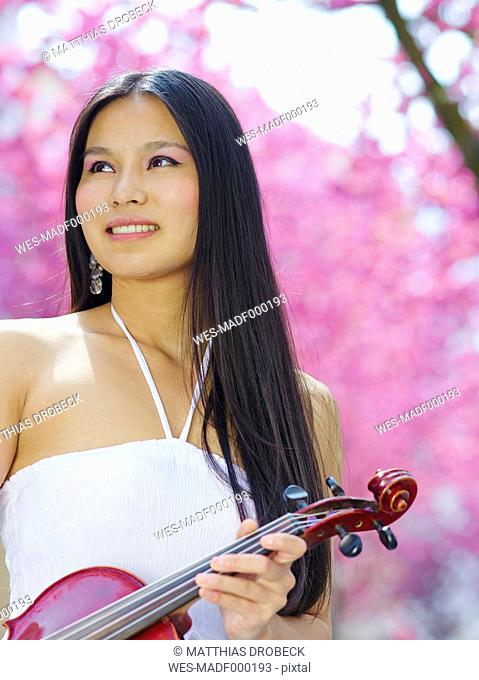 Portrait of young woman with viola in front of blossoming cherry tree