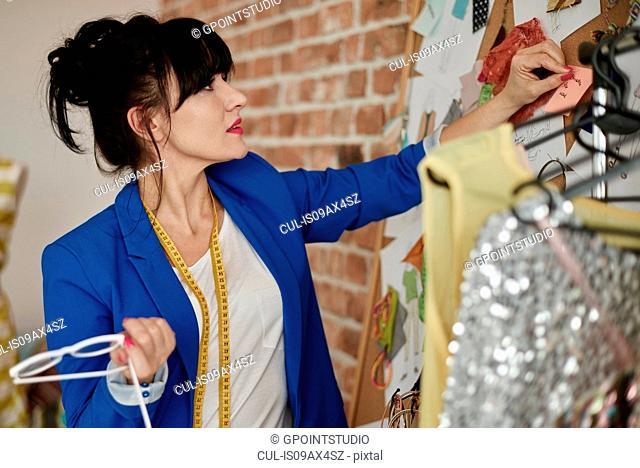 Woman in design studio looking at wall mounted mood board