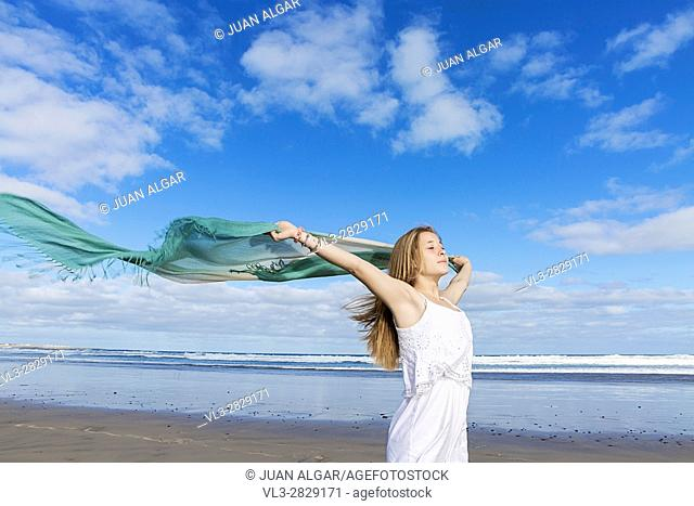 Horizontal shot of woman running with pareo on the beach