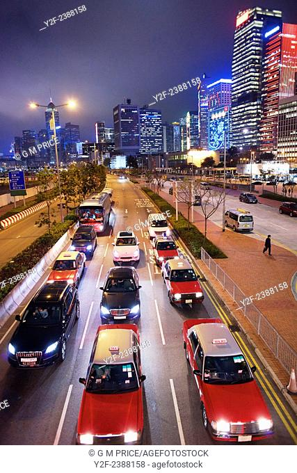 cars wait at traffic lights with Hong Kong skyline in the background