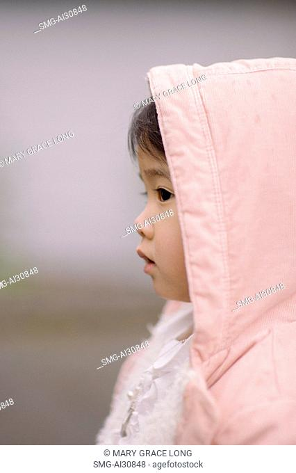 USA, Side-view of girl (2-3) in pink jacket