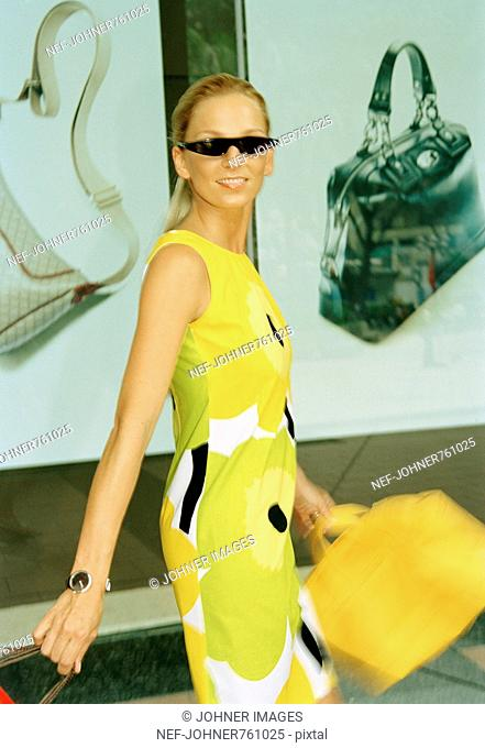 Woman dressed in a yellow dress going shopping, Singapore