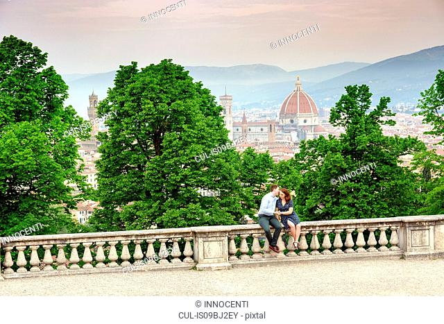 Young man kissing woman, Santa Maria del Fiore in background, Florence, Toscana, Italy