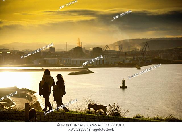Couple and dog walking in front of the Bay of Gijón from the Hill and Park of Santa Catalina (Gijón, Asturias, Spain, Europe) in the seaside neighborhood of...