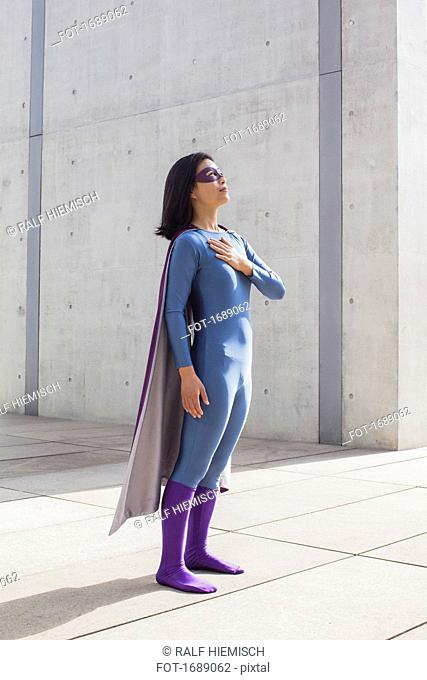 Confident woman wearing superhero costume standing on floor by wall