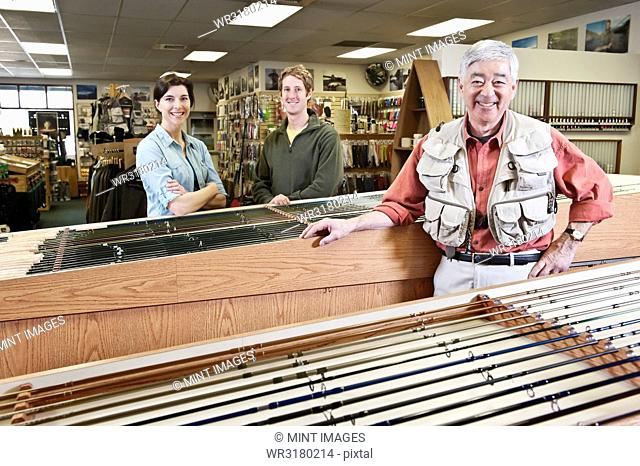 Asian American senior male owner of a retail fly fishing shop and Caucasian male and female employees in the background. Owner of the shop is wearing a fly...