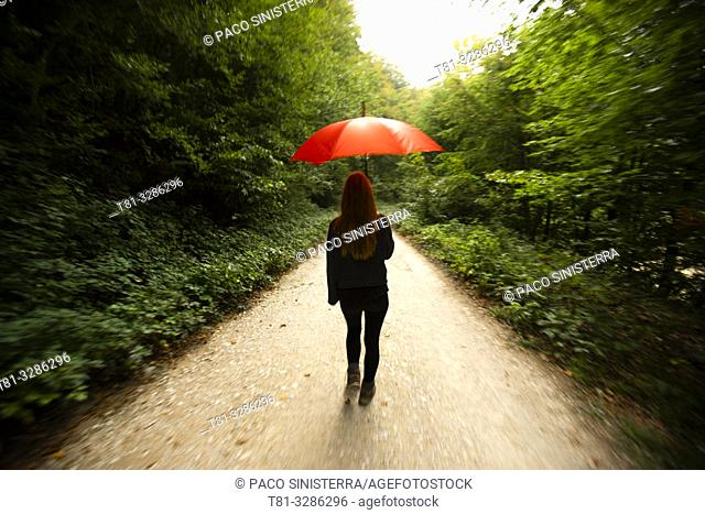 Young woman walking on forest path with red umbrella. Selva de Irati, Navarre, Spain