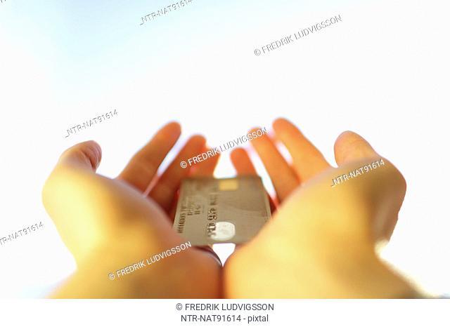 Hands holding gold credit card, studio shot