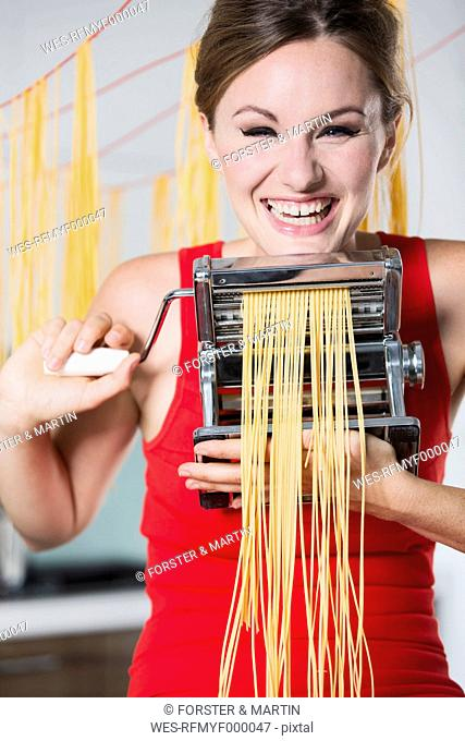 Germany, Young woman making pasta with machine