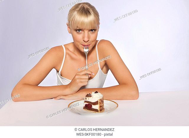 Young woman with slice of cake, portrait