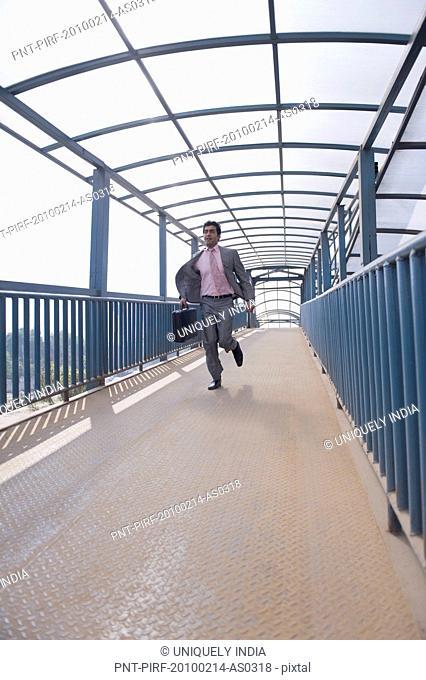 Businessman running on a footbridge, Gurgaon, Haryana, India