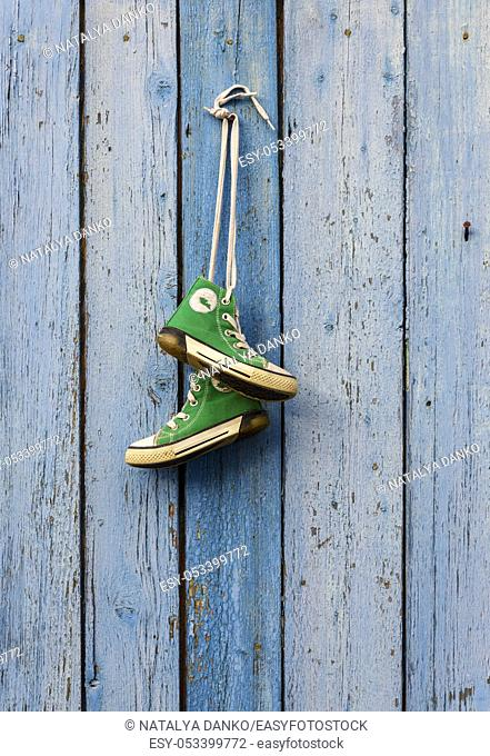 pairs of old textile green classic sneakers hang on a cord, blue shabby wooden background