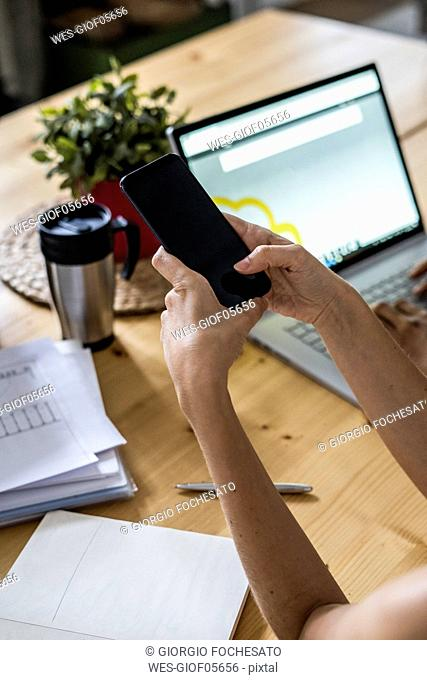 Close-up of woman using cell phone at table at home