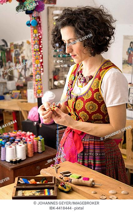 Button maker, young woman in colorful dirndl with Posamentenknopf Collier, sewing a nearly finished Posamentenknopf, in studio with Posamentenknopf supplies and...