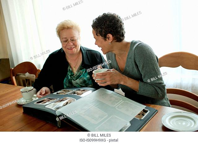 Mother and adult daughter looking through photo album