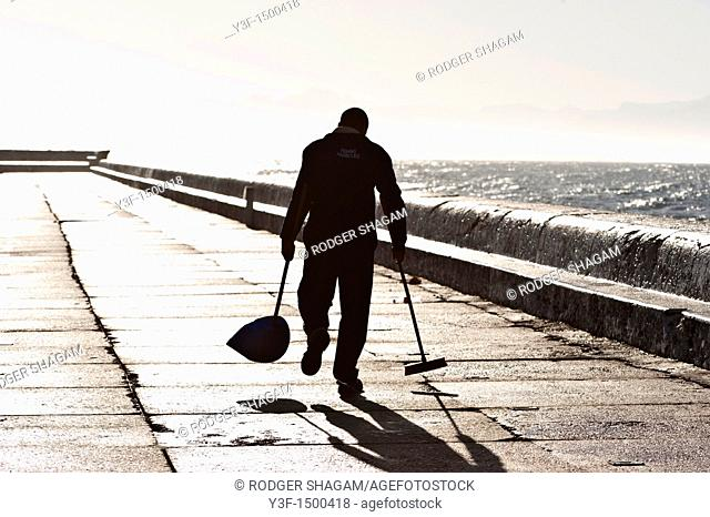 A cleaner walks along the harbour wall, slowly sweeping up rubbish left by fishermen the day before