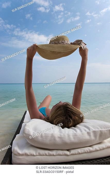 Woman relaxing on daybed at beach
