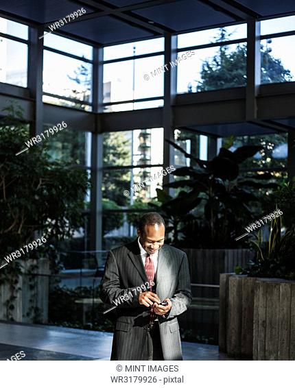 Black business man texting in a large lobby waiting area