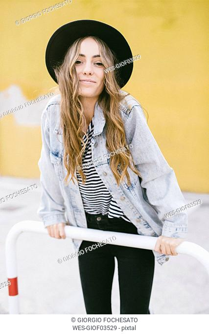 Portrait of fashionable young woman wearing hat