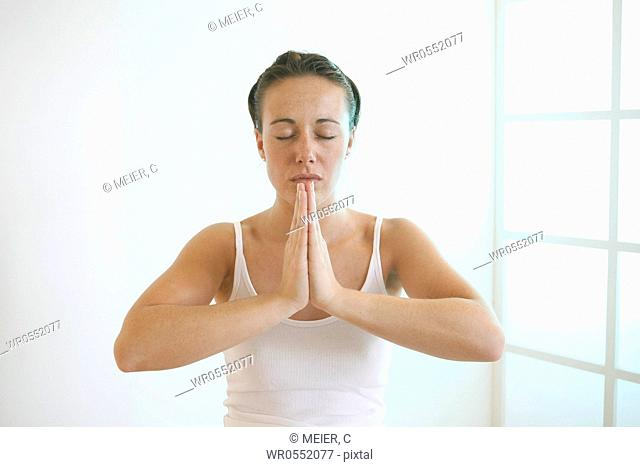 Young woman folds her hands meditatively in front of her chest