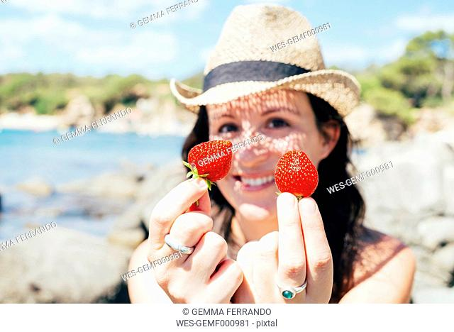 Hands of woman on the beach holding strawberries