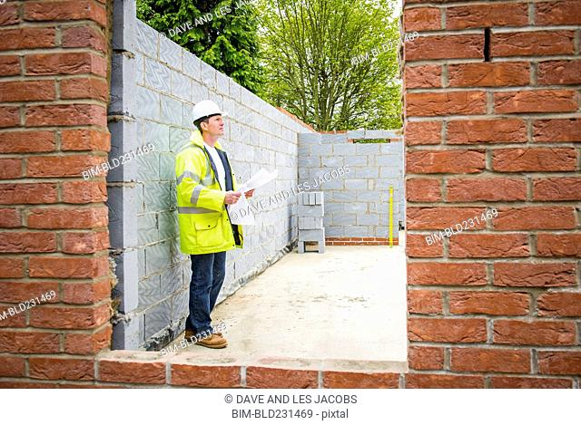 Caucasian construction foreman checking blueprint at brick wall